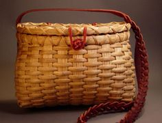 Gail Hutchison designer. This really darling purse basket is flat reed in an easy over under pattern. The lid is a duplicate of the base and is attached with leather cord and features a braided leather handle.  Two sizes for your choice.