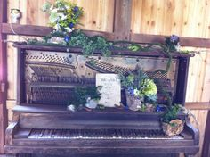Chic Floral Designs Blog.  A ruined piano decorated with ivy, succulents, lichen covered branches and other natural items for a barn wedding.  We happened on the piece of sheet music which was just perfect.