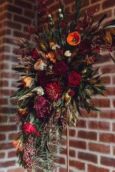Modern copper and burgundy wedding ceremony arbour flowers with tulips, roses and dahlias | Raconteur Photography