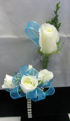 "Our ""sophisticated lady"" bracelet is the setting for this beautiful corsage.  The iridescent piping on this teal/aqua/turquoise ribbon really makes it pop.  We added silver baby's breath for a bit more sparkle.  White spray roses for her and a white rose for him.  Very elegant and sophisticated.  $47.98 for the set."