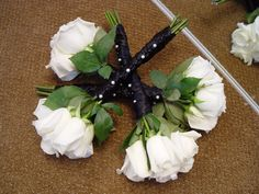 Bridesmaid's bouquets with white roses and black silk twisted warps accented with white and black pearls.