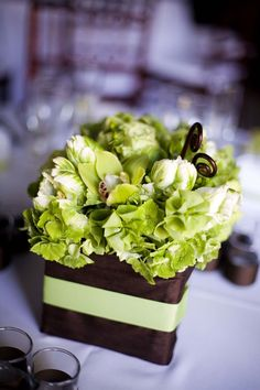 """Green floral centerpiece: Brown monkey tails added whimsy to the all green floral centerpieces (parrot tulips, bells of Ireland, hydrangea, cymbidium orchids and """"supergreen"""" roses)"""