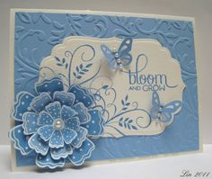 "supplies: 2 shades of blue and an ivory cardstock, Cuttlebug ""Victoria"" embossing folder, Hero Arts CG291 Three Dotted Flowers, F5042 Leaf Flourish, Verve VS-0144 Bloom & Grow, versamark ink and white embossing powder, Adirondack Stonewashed ink, Nesties Labels Four, Martha Stewart butterfly punch, pearls"