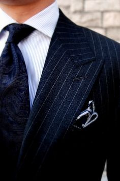 Blue chalk striped suit, striped shirt, dark paisley tie and patterned pocket square
