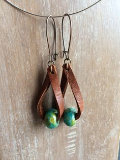 Hand cut beautiful distressed leather makes a loop I have strung a gorgeous turquoise Czech glass bead on! Its really hard to capture the colors of this bead! As always, the metal I use does NOT contain lead. Photo shows earrings with a penny so you have a guide of the size. These