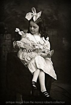 Girl holding doll with large bows in their hair.