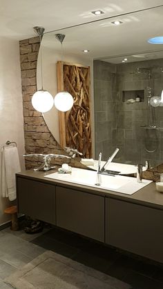 Rock bathroom with oversized mirror. Design by Veronique Jandrin