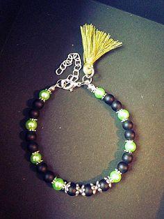 Bracelet femme fait main composé de perles en onyx mat, de perles en verres nacrées verts, de perles en métaux (sans nickel) et dun pompon vert. Le bracelet est ajustable grâce à sa chainette. Il mesure 18cm au plus court et 22cm au plus long. Envoyé avec un emballage pret à offrir. FRAIS DE