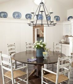 The owner of this California home commissioned copies of an antique ladder-back chair owned by a friend, then arranged them around the dining room's ebonized table; the wrought-iron candelabra is from Paul Ferrante. - CountryLiving.com