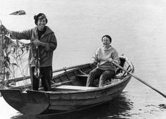 Tove Jansson and lady friend in a rowboat, laughing and fishing