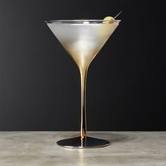 Shop Irina Gold Martini Glass.   Classic martini glass gets a metallic twist with a glam gold base and leggy stem that rises to a clear, wide rim.  Impresses guests at holiday cocktails and dressy dinner parties.