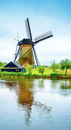 Traditional Windmill and water canal reflection in Kinderdijk, The Netherlands   |  13 Reasons Why The Netherlands Must Be On Your Bucket List