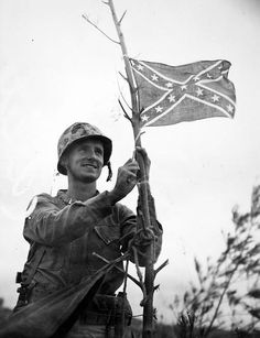Capt. Julius Dusenberg, USMC, raises the Confederate Stars and Bars at the top of Shuri Castle, Okinawa, May 29, 1945. When he raised the flag he let loose with a rebel yell. Most of his Marines joined in the yell.