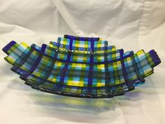 This is a woven glass bowl in blues and yellows.  I call it my Navaho bowl. It is 12 inches long and 8 inches wide.