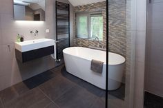Deze warme badkamer is ingericht met een prachtig ontworpen ovaal bad. Tot rust komen gaat prima in de duurzame Finse sauna van HARVIA.