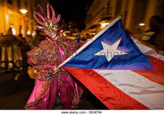 A costumed reveler called vejigante dances in the street with a Puerto Rican flag during the Carnaval de Ponce February - Stock Image
