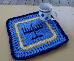 Hanukkah Placemat Crochet Pattern features decorative Menorah motif. Instant download of 8 page PDF with Graph. Using an intarsia method, similar to tapestry crochet, you will create the Menorah design. The motif is first worked in rows and then finished with a border worked in rounds around the square motif. This is a fun and interesting pattern to work. You'll want to make one for your own Hanukkah celebration and several to give as gifts!