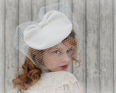 1940s Style White Tilt Hat with Veil by Jaya Lee  This dramatic veiled tilt hat was inspired by an actual vintage hat from the 1940s. The original hat was brown, but my version of the hat is alabaster white, as I feel this hat would make a stunning headpiece for a vintage bride! The hat sits on top of the head and tilts to the right, it is held in place by an elastic band that goes under the back of the head underneath the hair. The top of the hat is gathered up into a bow like shape with a…
