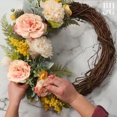 We'll show you how to make a farmhouse wreath to dress up your front porch for the season. You can use real flowers, but we paired faux blooms with a classic grapevine wreath to create a front door wreath that'll last for years to come. Finish the handmade spring wreath with a gray buffalo check bow. #diyideas #homedecordiy #diywreath #frontdoordecor #springwreath #bhg