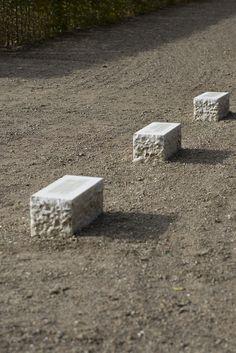 #Schleswig Drei grob behauene Quader aus weißem Marmor stehen in einer Reihe nebeneinander auf dem höchsten Plateau im Gottorfer Barockgarten. Bildhauer Arne Rautenberg polierte jeden der drei Quader auf der Oberseite glatt und fügte eingemeißelte Inschriften hinzu.