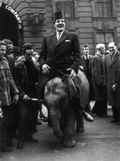 Tommy Cooper riding a three year old elephant from Billy Smart's circus, High Holborn, 1959.
