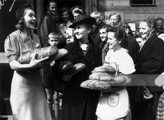 German women leaving the baker's shop with arms full of bread. White bread has arrived in Berlin for the first time since the end of the war and is being distributed by the US authorities.