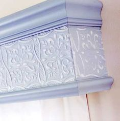 Top It Off  To add interest to a premade wooden cornice, use a border paper or cut a roll to size. Cornices typically come finished, so buy one in white and repaint in the color of your choice. Paint the paper; let dry. Paste paper to the cornice, using the tip of a scissors to tuck the edges under the molding.