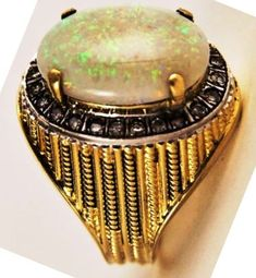 Elvis Presley's massive 14KT gold vintage ring featuring a beautiful crystal opal surrounded by approximately 1.25ct of diamonds. Elvis bought it from Thunderbird Jewelers in Las Vegas in the early 1970s, and he wore it both on and off stage for years. Via elvisblog.net/.