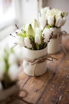 white tulips in cute vases with twine detailing on a window sill for spring / http://www.himisspuff.com/white-tulip-wedding-ideas-for-spring-weddings/9/