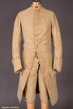 "GENT'S PRINTED CREAM VELVET SUIT, ENGLAND, 1770s  Two piece suit of horizontally ribbed silk velvet with pink and green dots: collarless coat with self covered button trim, 5.5"" deep cuffs, shaped pocket flaps, cream silk lining; narrow fall-front breeches with cut steel buckles at knees, napped cotton-linen lining, (stains and repairs underarms, extensive damage and repairs to breeches) coat good, breeches fair."