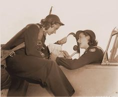 Two women pilots, part of the WASP program, talk business before a flight. The photo is part of an exhibit at Fantasy of Flight in Polk City, Florida.