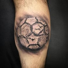 Tatuagem de uma bola de futebol desgastada.