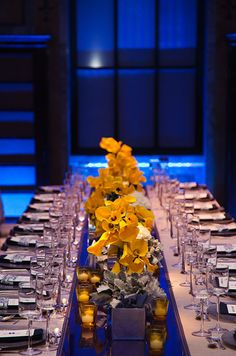 Long banquet tables are covered in gray linens and punctuated with amix of blooms atop a cobalt blue runner.