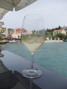 A beautiful glass of wine in Fiskardo, Kefalonia, Ionian Islands, Greece pic taken by Leanne & Bella Blue Pine Forest, Simple Pleasures, Home And Away, White Wine, Islands, Greece, Backdrops, Alcoholic Drinks, Foods