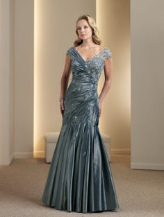 Taffeta and lace modified A-line gown with tip-of-the-shoulder V-neckline, cap sleeves, directionally ruched bodice accented with hand-beaded appliqués, dropped waistline, full asymmetrically pleated skirt. Matching shawl included (not shown). Sizes: 4 – 20