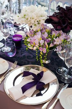 Crisp white dinner napkins are folded and bound with an elegant purple ribbon.