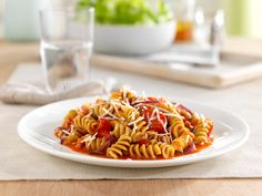 1 box Barilla® Veggie Rotini  4 tablespoons extra virgin olive oil  1 small red onion (cut julienne)  1 pint halved red cherry tomatoes  1 pint halved yellow cherry tomatoes  3 ounces diced Pancetta*  Salt and black pepper to taste  ½ cup shredded Pecorino Romano cheese