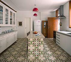 O ladrilho hidráulico estampado reveste todo o piso da cozinha e a ilha central, construída em alvenaria. Projeto do arquiteto Carlos Verna