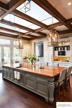 Splendid oversized island with butcher block top and skylights above. The trim on the skylights complements the beautiful hardwood floor. Lovely traditional kitchen.
