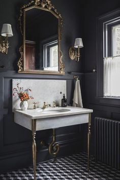 Gorgeous old-world bathroom in charcoal gray and white with a cool marble and brass console sink. Really well-done!