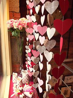 Valentines Day window display with hanging paper heart garland.