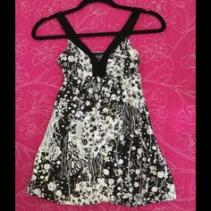 Halter top in black, white and silver Halter top in black white and silver. Black accent straps with black white and silver floral design. Very. Cute and flowy. Fully lined. Great construction. Size Small. Excellent condition. Tops