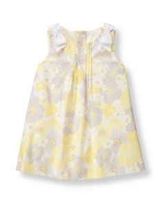 Sweet blooms decorate our dress in airy poplin chintz. Pintucked bib and grosgrain ribbon shoulder bow accents finish the darling design.
