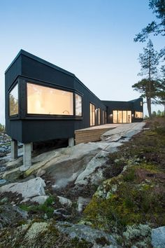 pS Arkitektur have designed Villa Blåbär, a house located in Nacka, Sweden | timber structure sits atop concrete footings and rough rocky landscape