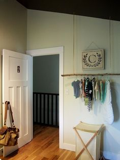 A hanging branch holds baby clothes in a girl's nursery. And, love the minty green clothes hangers.