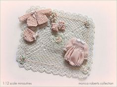 1:12th scale miniature baby clothing ... hand knitted wool sweater set, hand crocheted baby blanket, and a hand-sewn romper.