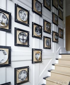 Fornasetti plates in custom Lucite-and- nickel frames line the stairwell; the wall is painted in Ralph Lauren Paint's Brilliant White.