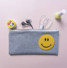 Our Sporty grey jersey zip pouches are embellished with retro slogan patches.  Retro Smiley Face personalised zip pouch pencil case Made and Designed in our London Studio - a practical stand out piece which would grace any desk or bag. Great for make up, small stationary items, tech accessories, jewelry or as a travel wallet. Practical and stylish in contemporary grey jersey with retro patches and a chunky metallic zip.  Can be personalised with an initial zip pull, please choose this option…