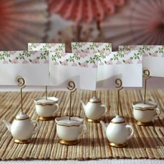 Kate Aspen's Tea Time Whimsy Place Card Holders, available in sets of 6, add a delightful touch to your tea party table decor. Each set of place card holders comes with 3 teapot and 3 teacup shaped bases—all crafted with sturdy resin—to keep the matching floral place cards upright for all to see. split Features and Facts: White teapot- and teacup-shaped place card holders with gold foil details. Included place cards feature a pink floral design on a white background. Metal spiral stem holds plac Bridal Shower Tea, Tea Party Bridal Shower, Teacup Crafts, Tea Party Table, Autumn Tea, Tea Party Birthday, Birthday Ideas, Party Table Decorations, Baby Shower Fall