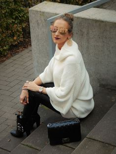 SHADES OF K by Karen  wearing black vinyl pants, creme white wool sweater with statement sleeves, mirrored sunglasses, hoop earrings, stacked bracelets, and buckled black boots.